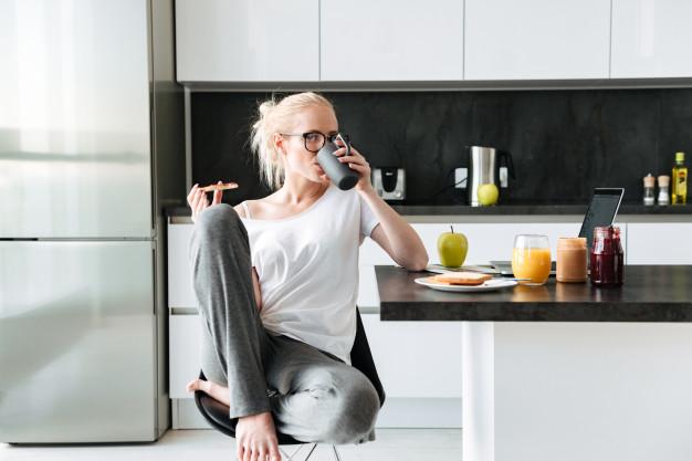 Mujer sentada sobre taburete desayunando en su cocina Gradén